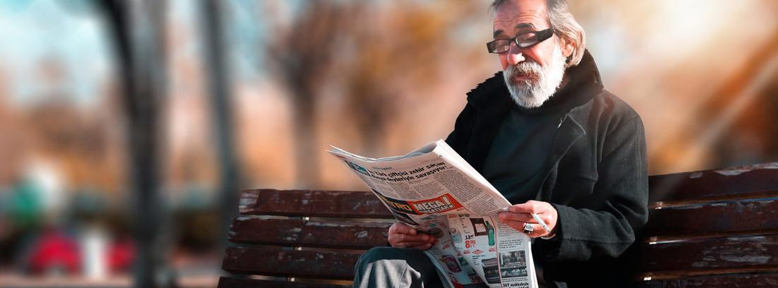 Hombre con barba y pelo blanco en banco de parque leyendo periódico