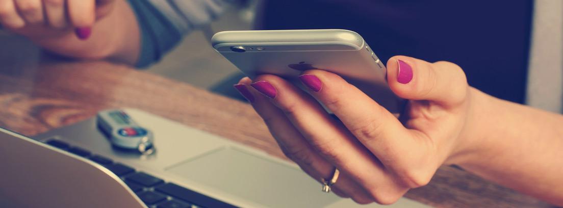 Persona con móvil en la mano y delante de ordenador portátil