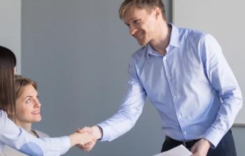 Jefe joven dando la mano a una empleada