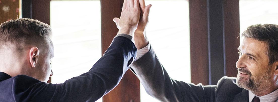 Dos hombres de distinta edad chocando la mano