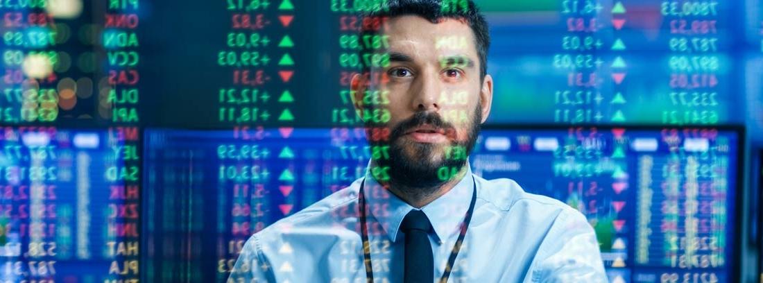 Hombre con camisa azul frente a pantallas de mercados financieros