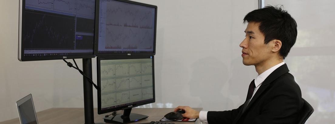Hombre con chaqueta negra frente a diferentes pantallas de ordenador con gráficos