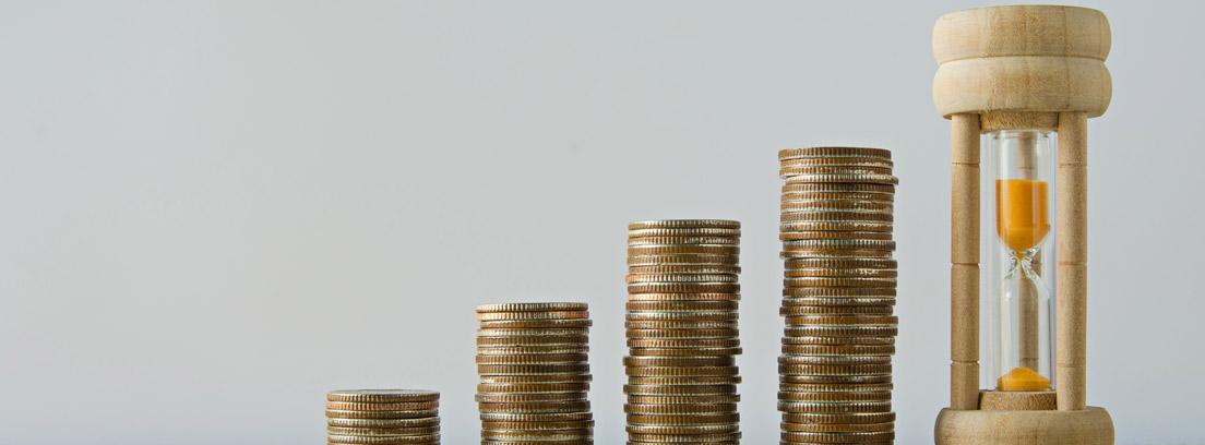 Monedas apiladas de menor a mayor y un reloj de arena