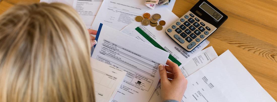 Vista cenital de una mujer mirando facturas con calculadora un monedero