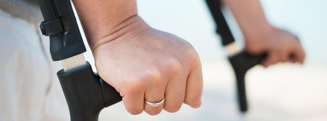 Vista parcial de unas manos apoyadas en unas muletas