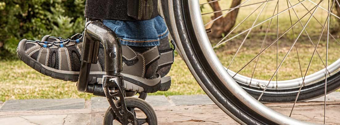 Pies apoyados en el reposapiés de una silla de ruedas