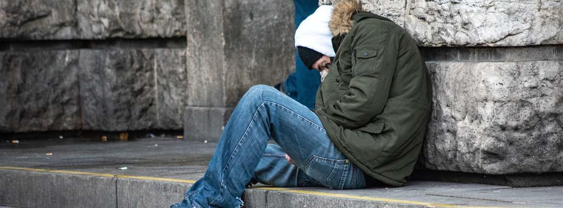 Persona sentada en unas escaleras en las calle y apoyada en la pared