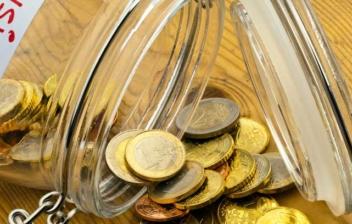 """Tarro de cristal con monedas cayendo y con una etiqueta en la que pone """"pension"""""""