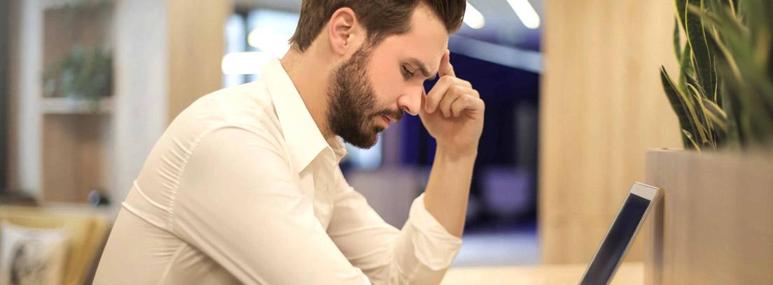 Hombre sentado con gesto preocupado frente a un ordenador