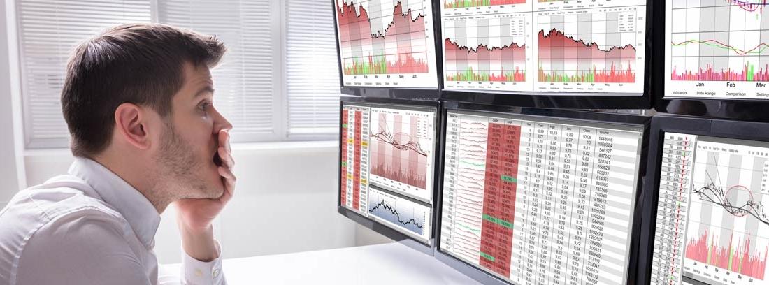 Hombre con gesto preocupado mira pantallas con gráficos económicos en rojo