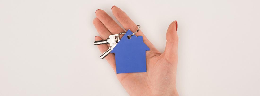 Mano mostrando un llavero azul con forma de casa