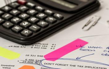 Calculadora sobre papeles con cifras y apuntes contables