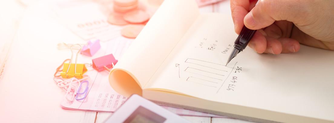 Mano con pluma haciendo cuentas sobre papel y junto a calculadora