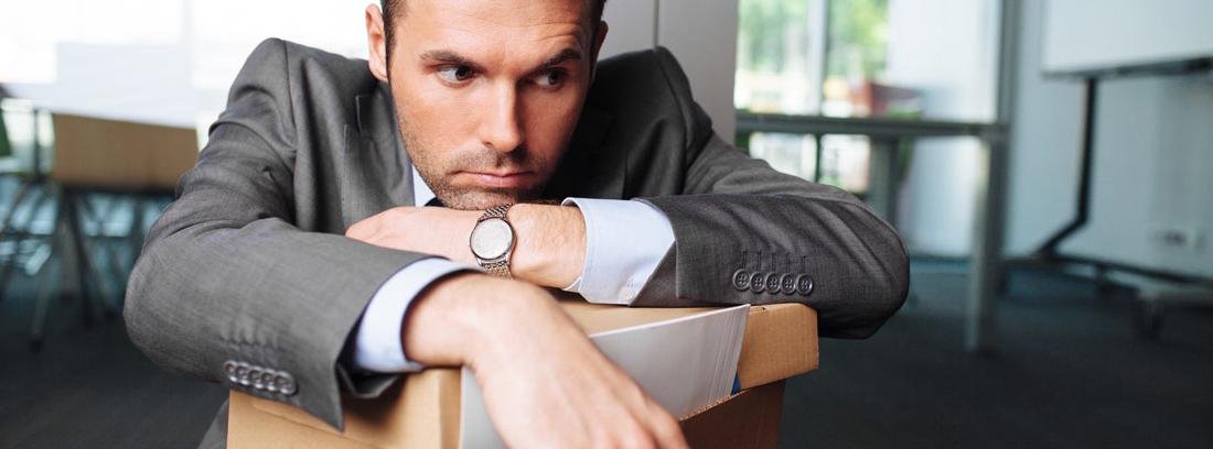 Hombre con gesto serio apoyado sobre una caja con papeles
