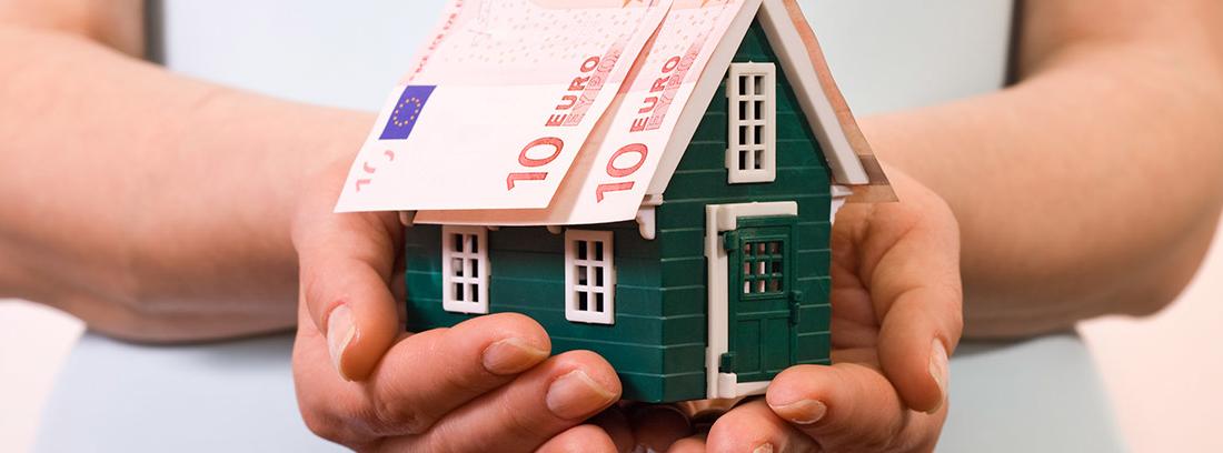 Manos sujetando una casa de juguete con unos billetes de 10 euros en el tejado