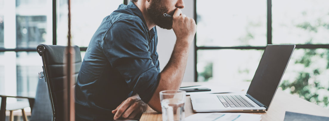 hombre pensativo frente a una pantalla de ordenador