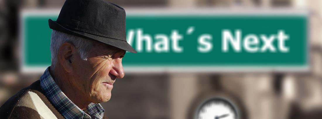 Hombre mayor con un cartel detrás y un reloj