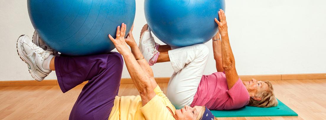Dos mujeres en una clase de Pilates sosteniendo una pelota