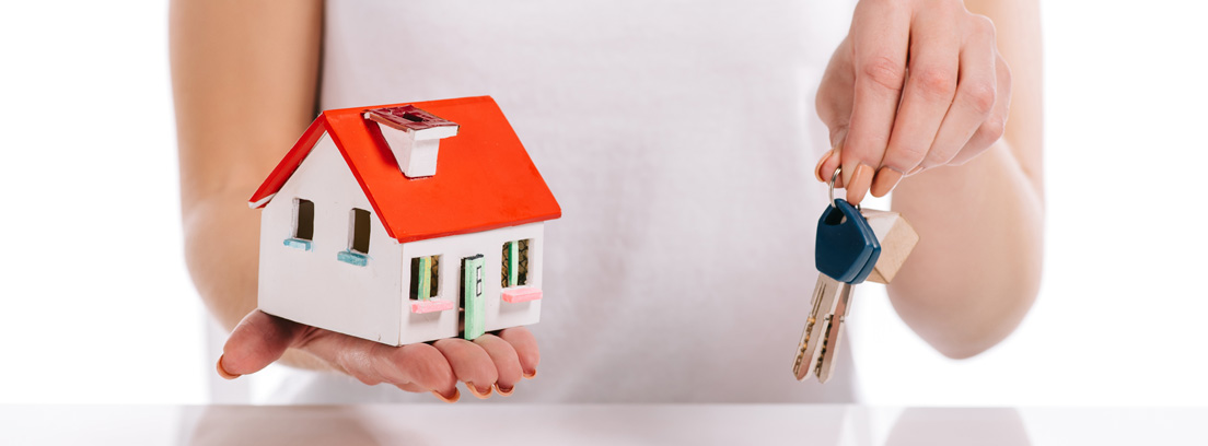 Mujer sosteniendo una maqueta de una casa y unas llaves