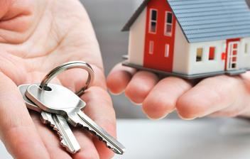 Manos sujetando unas llaves y una maqueta de casa