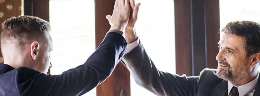 Dos hombres con traje estrechando las manos como muestra de acuerdo tras una buena negociación