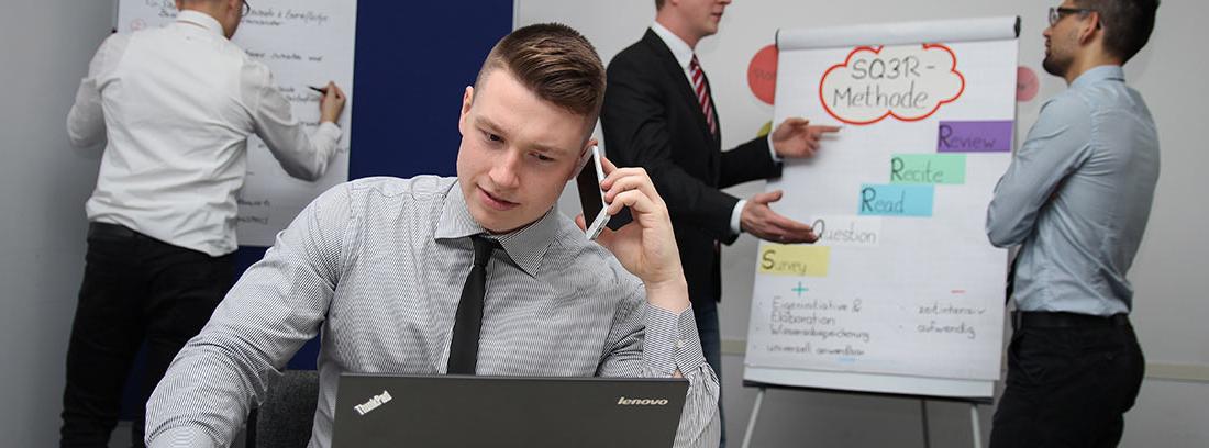 Hombre sentado frente a portátil y otros detrás delante de paneles con información