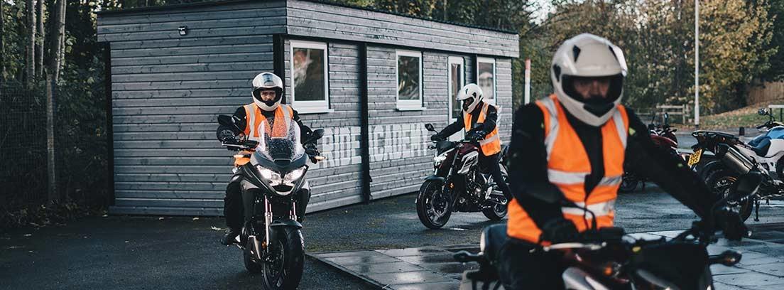 Grupo de motoristas con uniforme oscuro y chaleco naranja