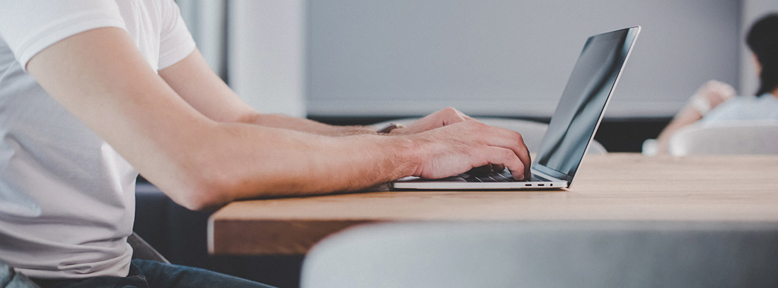 Hombre escribiendo en su ordenador