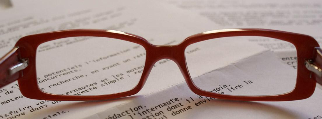 Gafas rojas sobre papel impreso con texto