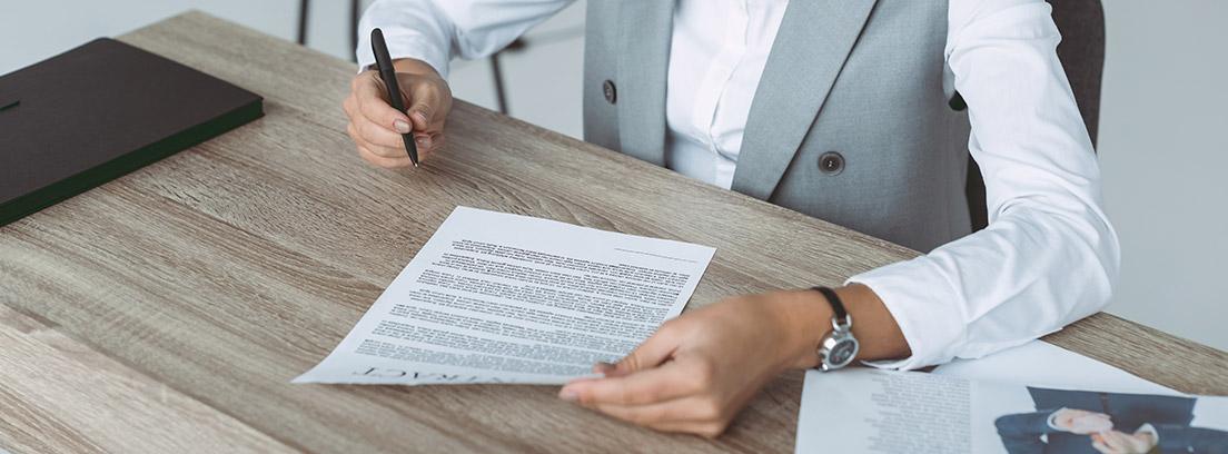 Mujer con papel en una mano y bolígrafo en otra