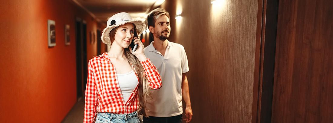 Hombre y mujer con maletas en un pasillo al lado de una puerta