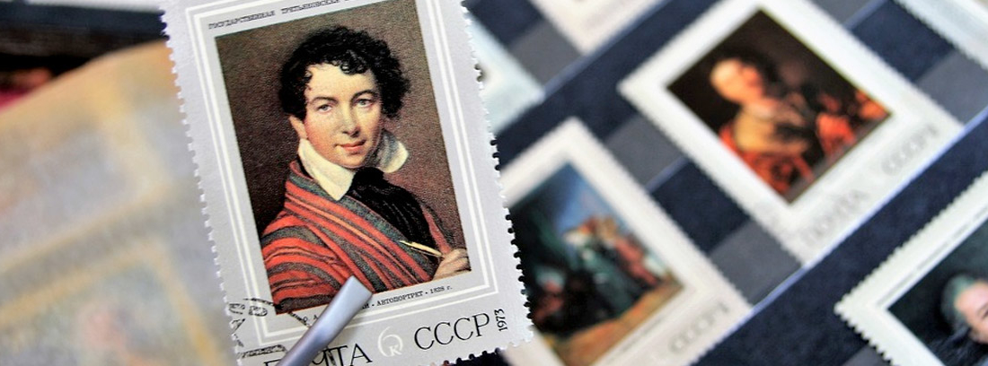 Pinza de filatélico sujeta un sello delante de otros