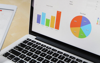 Ordenador portátil con gráficos financieros junto a tableta con calendario