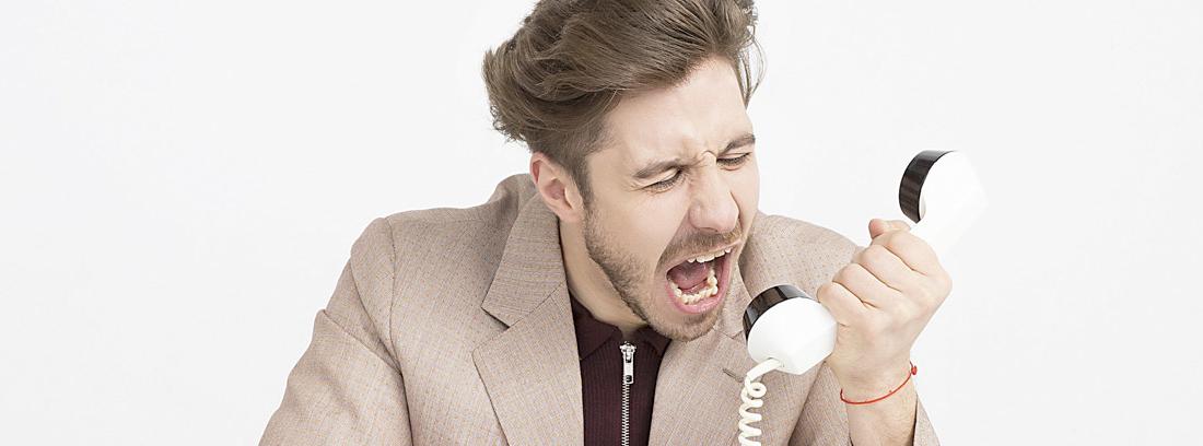Hombre grita hacia auricular de teléfono fijo clásico de color blanco