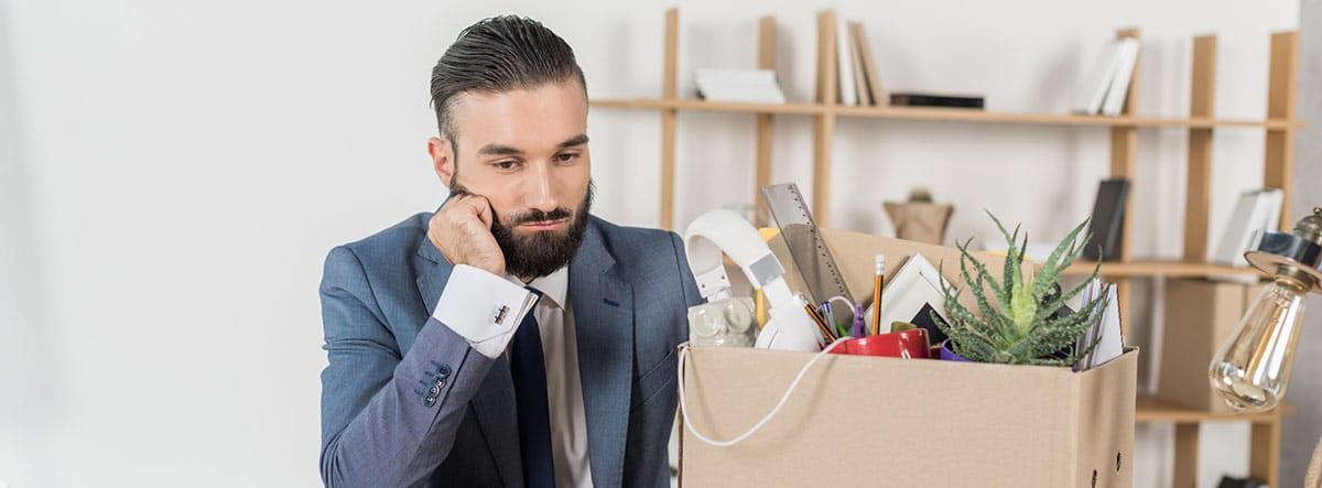Hombre con barba recogiendo en una caja sus pertenencias en una oficina