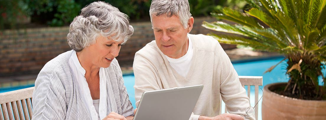 Dos jubilados usando un ordenador portátil