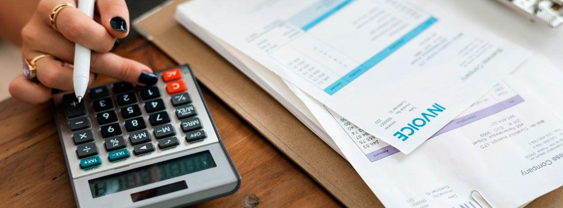 Mesa con papeles y mano de mujer sobre una calculadora