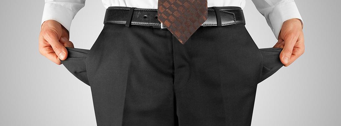 Hombre con traje sacando el interior de los bolsillos de su pantalón