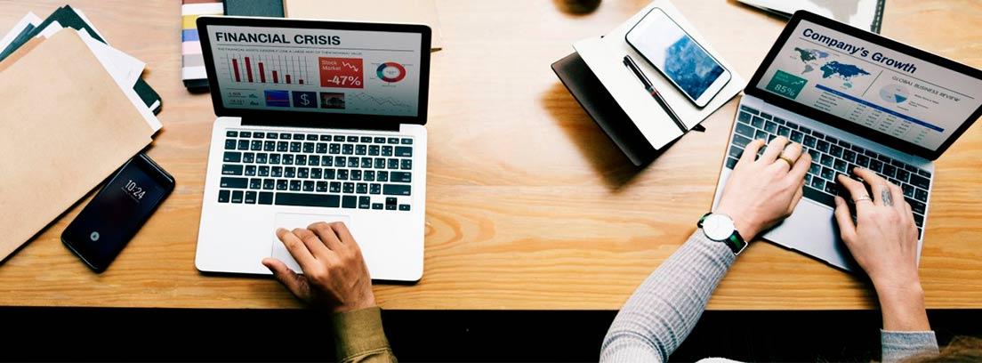 Vista cenital de una mesa con ordenadores y objetos de oficina
