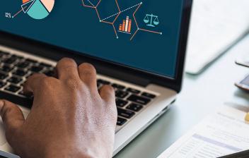 Manos sobre teclado de ordenador portátil con imágenes de gráficos en pantalla