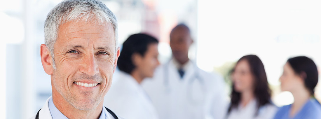 Médico sonriente con pelo blanco