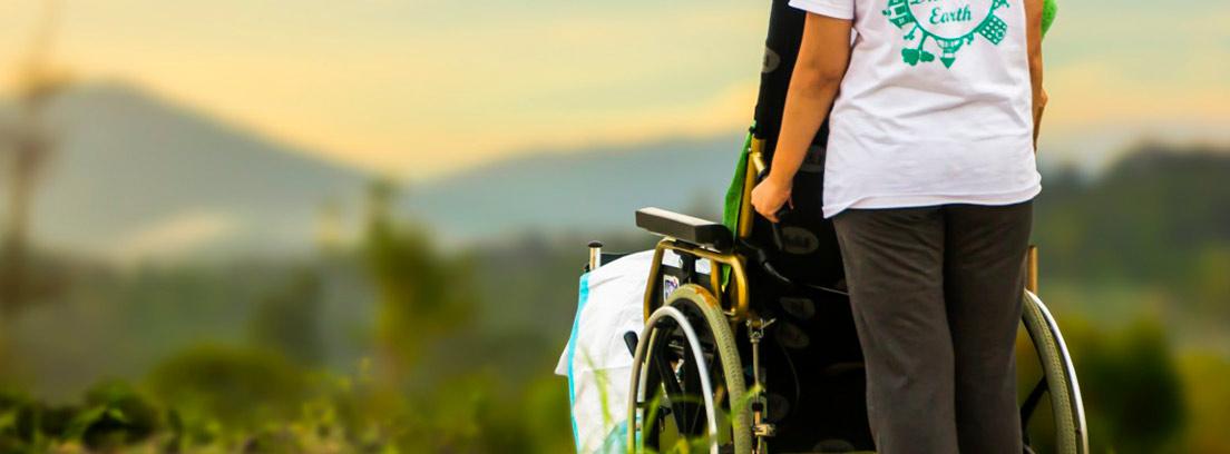 Mujer de espaldas llevando una silla de ruedas por el campo