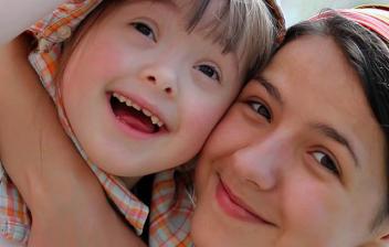 Primer plano de mujer y niña abrazadas con gesto alegre
