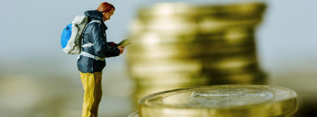 Figura de un hombre con mochila leyendo un libro sobre columnas de monedas de euro