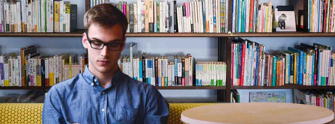 Hombre con gafas sentado delante de una librería