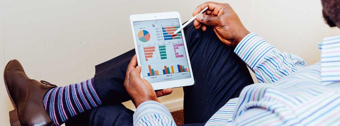 Hombre sentado mira gráficos en una tableta