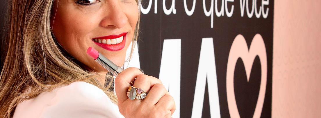 Mujer sonriente con un pintalabios en la mano