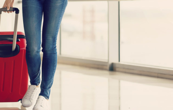 Vista parcial de las piernas de una mujer caminando por un pasillo junto a una maleta