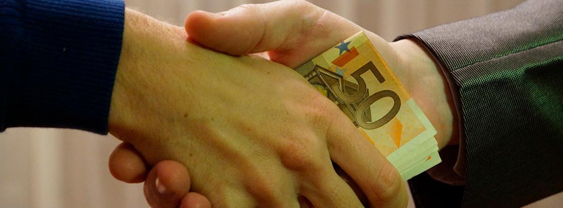 Manos dando billetes a otra mano