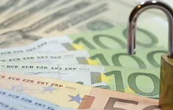 Billetes de euro en abanico con un candado abierto encima